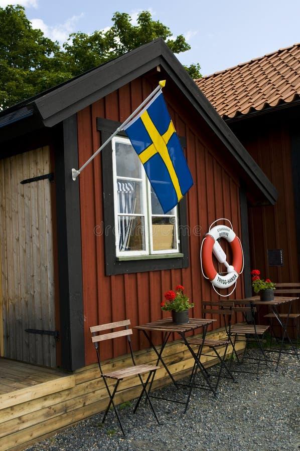 Hutte de plage avec le drapeau suédois et bouée de sauvetage en Suède images stock