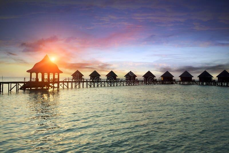 Hutte de silhouette au-dessus de l'eau de mer tranquille transparente sur un coucher du soleil maldives photographie stock libre de droits
