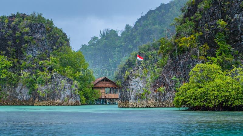 Hutte en bambou entre quelques roches sous la pluie dans la baie, îles de Painemo, Raja Ampat, Papouasie occidentale, Indonésie photographie stock libre de droits