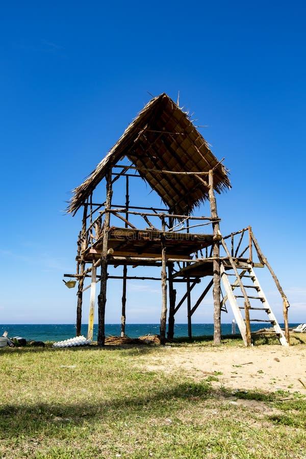Hutte en bois au jour ensoleillé au-dessus de la plage sablonneuse tropicale et du ciel bleu b image libre de droits