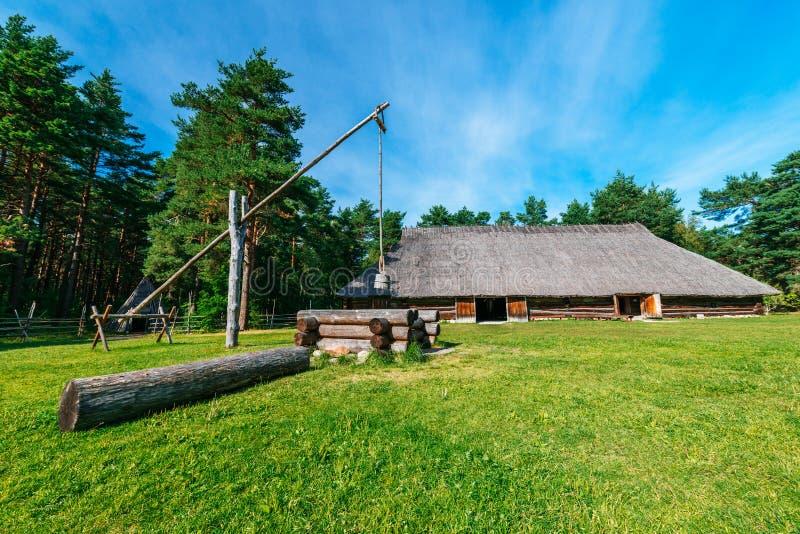 Hutte et puits traditionnels de pays photo stock