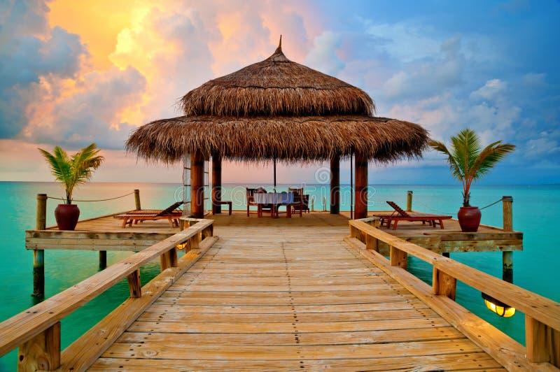 Hutte tropicale sur l'eau au coucher du soleil photographie stock
