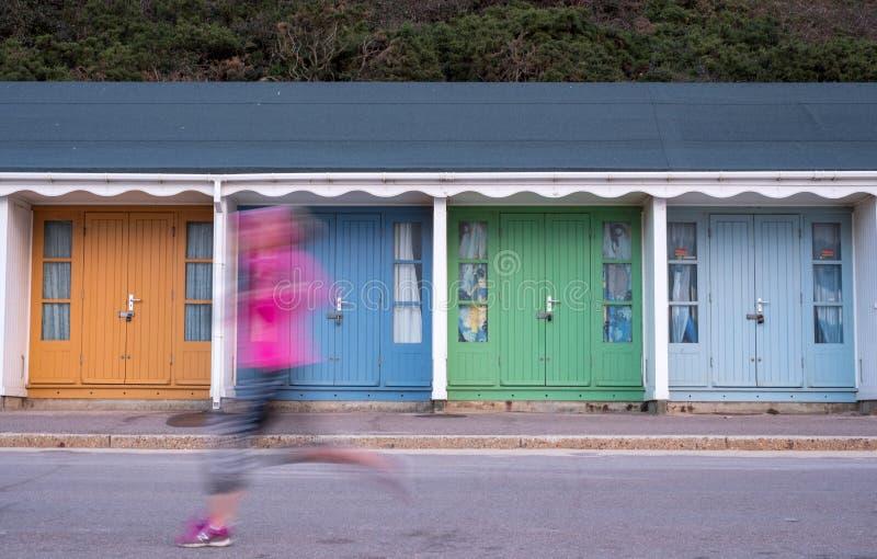 Huttes colorées de plage avec le coureur dans l'avant, situé sur la promenade sur le bord de mer BRITANNIQUE de Bournemouth photo stock