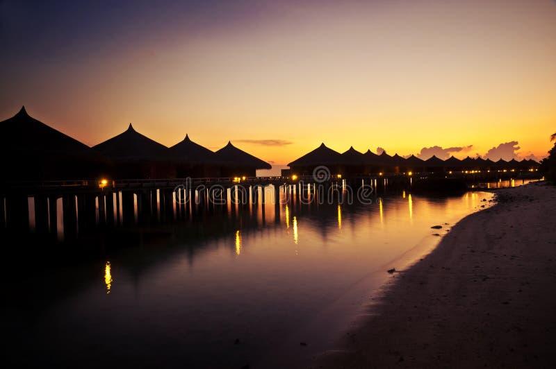 Huttes tropicales le long d'une plage au coucher du soleil photos stock