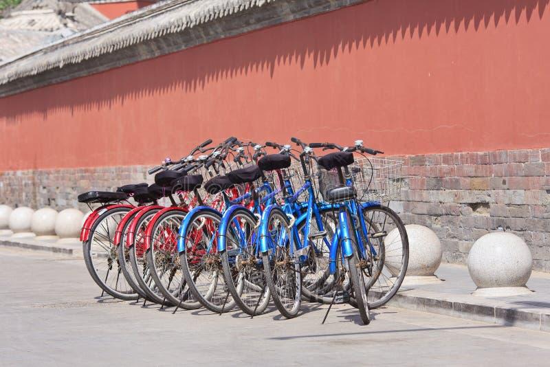 Huurfietsen dichtbij een historisch gebouw, Peking, China worden geparkeerd dat stock foto
