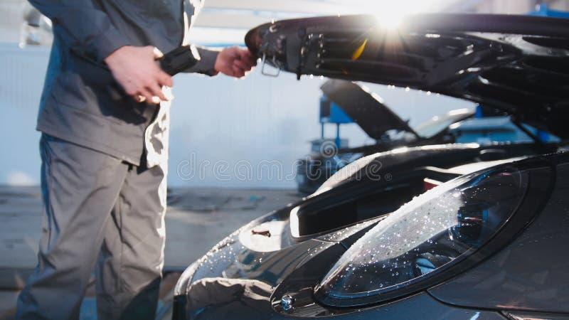 Huv för den bil- mekanikern för lyxig sport i bilgarage royaltyfri fotografi