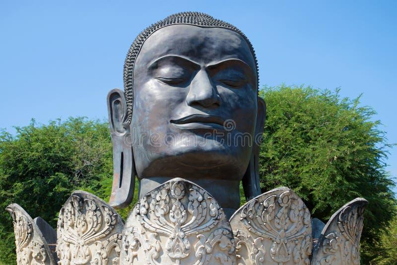 Huvud av den svarta Buddha i closeupen för lotusblommablomma Forntida skulptur i den buddistiska templet av Wat Thammikarat Ayutt arkivbild