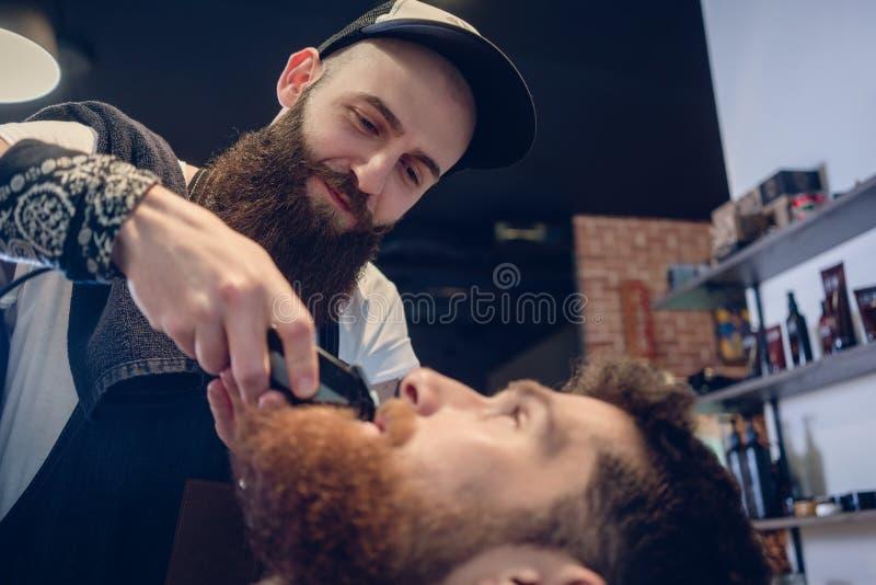 Huvud av en man och handen av en barberare som klipper hans skägg arkivfoto