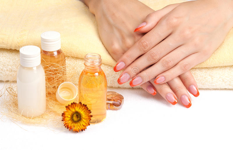 Huvuddelomsorg: orange manicure arkivfoton