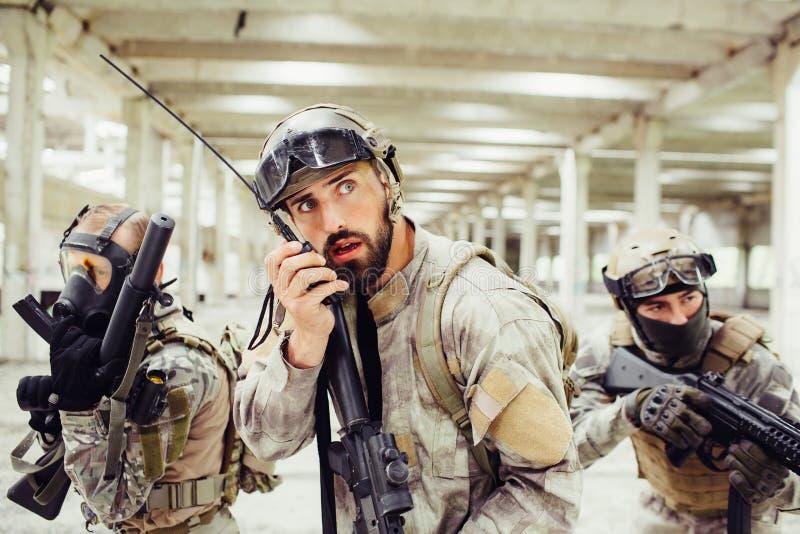 Huvudet av soldater rymmer geväret i händer och talar till den bärbara radion Han ser upp till sidan Andra två grabbar fotografering för bildbyråer