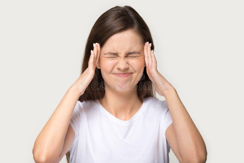 Huvudet skott somståenden belastade kvinnan som trycker på tempel, lider från huvudvärk royaltyfri bild