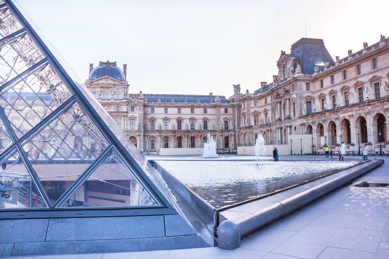 Huvudsaklig borggård av Louvremuseet med pyramiden och springbrunnen paris royaltyfri fotografi