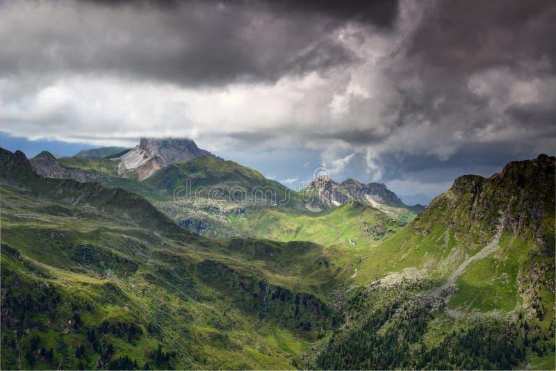 Huvudsaklig kant för Carnic fjällängar under den mörka molnÖsterrike Italien gränsen arkivbild