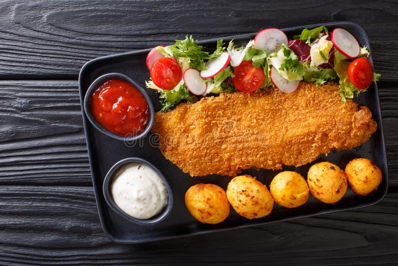 Huvudsaklig kurs av torskfil?n, i att panera med en garnering av nya potatisar och salladn?rbilden f?r ny gr?nsak horisontalb?sta royaltyfria bilder