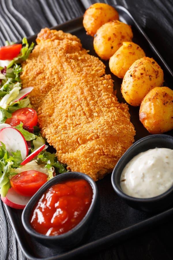 Huvudsaklig kurs av torskfil?n, i att panera med en garnering av nya potatisar och salladn?rbilden f?r ny gr?nsak vertikalt royaltyfri bild