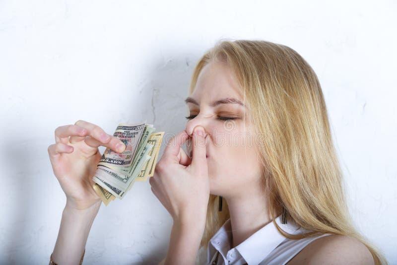 Huvudskott av den blonda europeiska kvinnan som luktar kassa royaltyfri bild
