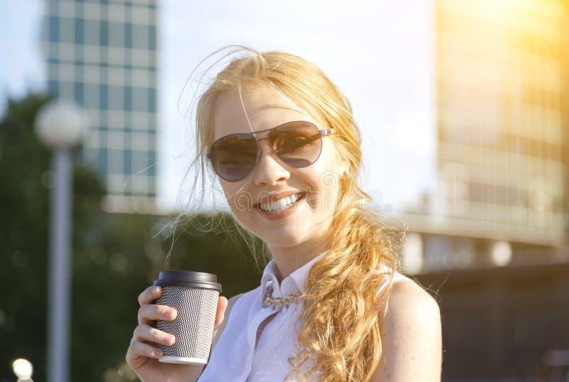 Huvudskottstående av den unga kvinnan som dricker kaffe på stadsgatan arkivbilder
