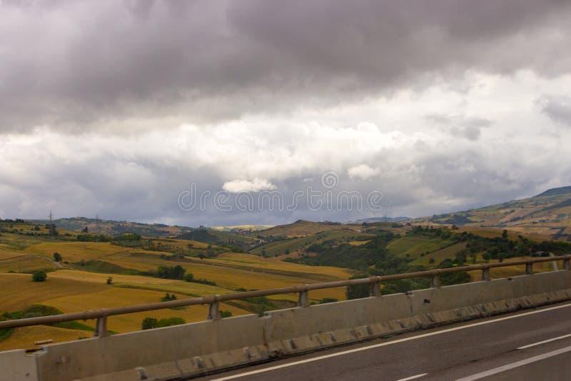 Huvudväg över filelds på molnig dag Grå färgen fördunklar över gula medows lantlig liggande Bygdbakgrund royaltyfri foto