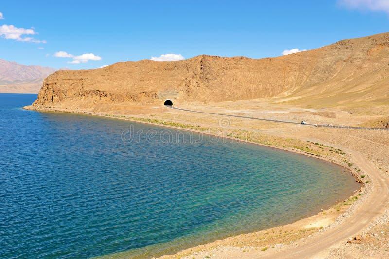 Huvudväg längs bergsjön i Tibet royaltyfria bilder