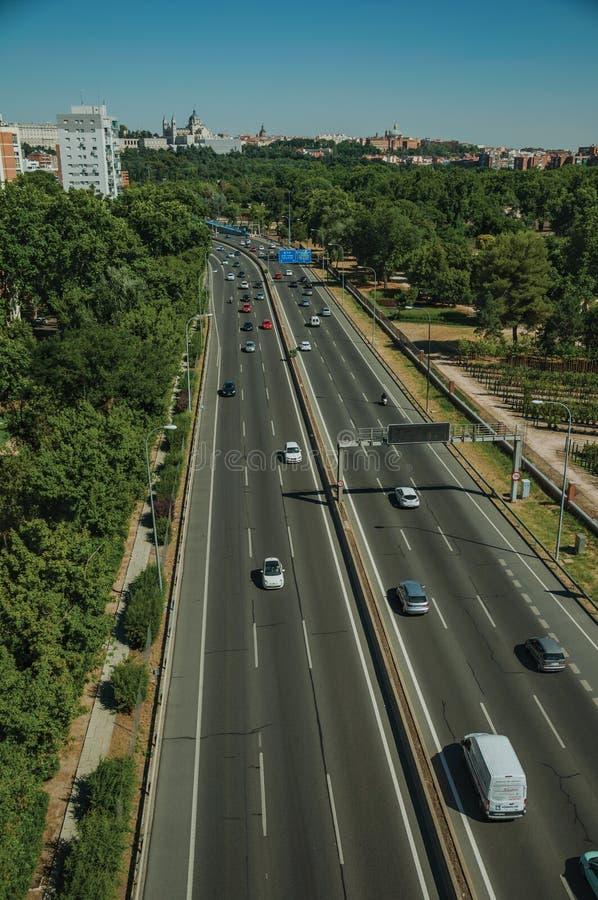 Huvudväg med tung trafik i mitt av träd på Madrid fotografering för bildbyråer