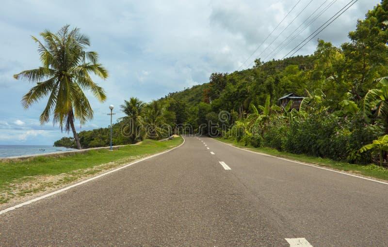 Huvudväg på den tropiska ön Kust- väg i eftermiddagen Tom väg vid sjösidan fotografering för bildbyråer
