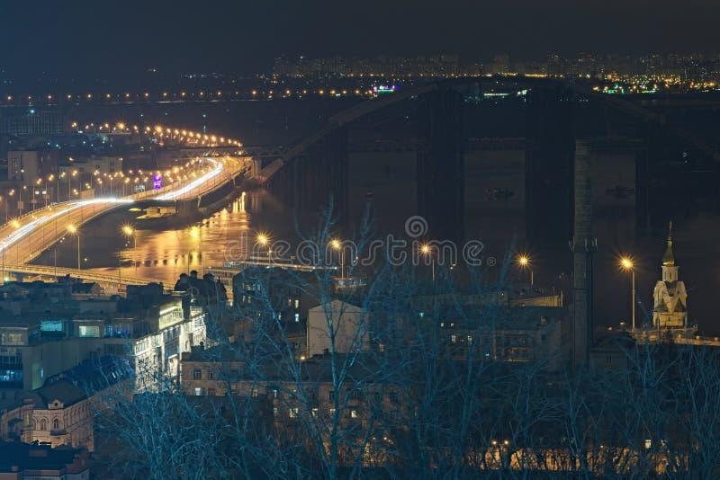 Huvudväg på natten längs den Dnieper floden med spårämnar och ljus, havannacigarrbron och den Naberezhno-Kreschatitska gatan i Ky arkivbild