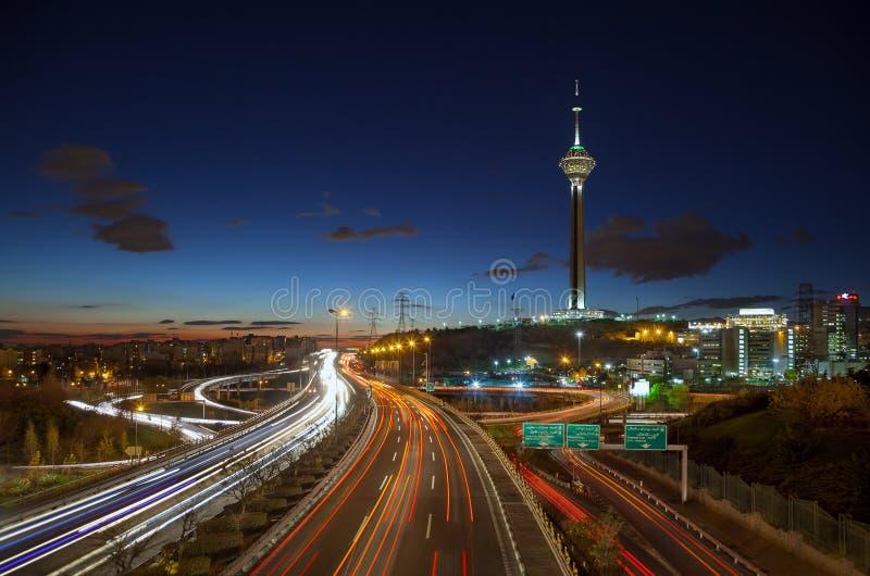 Huvudvägar av Teheran fyllde med övergående bilar som var främsta av Milad Tower mot blå himmel med moln fotografering för bildbyråer