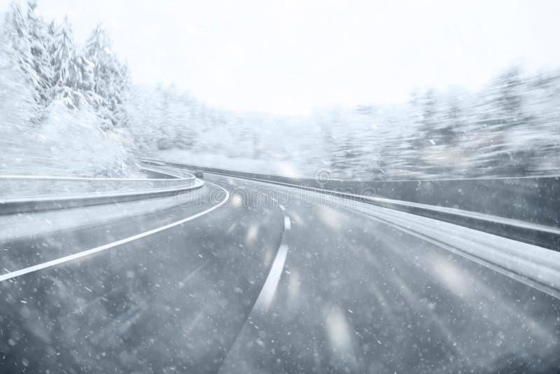 Huvudvägbilkörning på den snöig dagen royaltyfri fotografi