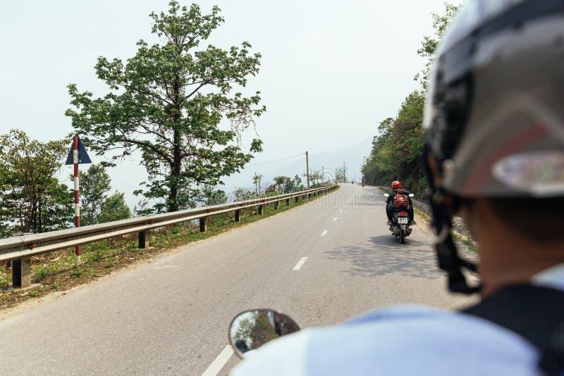 Huvudvägen med busken och träd längs vägen, som beskådar bak motorcykelchauffören i sommar på Sa-PA, Vietnam royaltyfria bilder