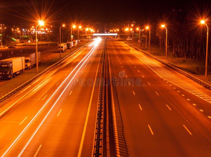 Huvudvägen väg på natten, ljus skuggar på motorväg arkivfoto