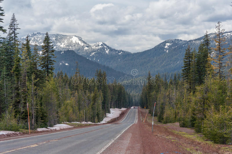 Huvudvägspring till och med skogar av Oregon täckte med snö USA arkivfoto