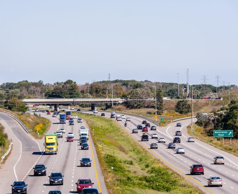 Huvudvägtrafik nära ramper och planskild korsning i Burlington, Ontario, Kanada royaltyfria bilder