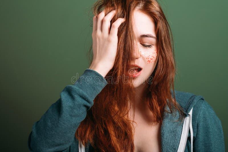 Huvudvärk för blick för smutsigt hår för ung kvinna trött royaltyfria bilder