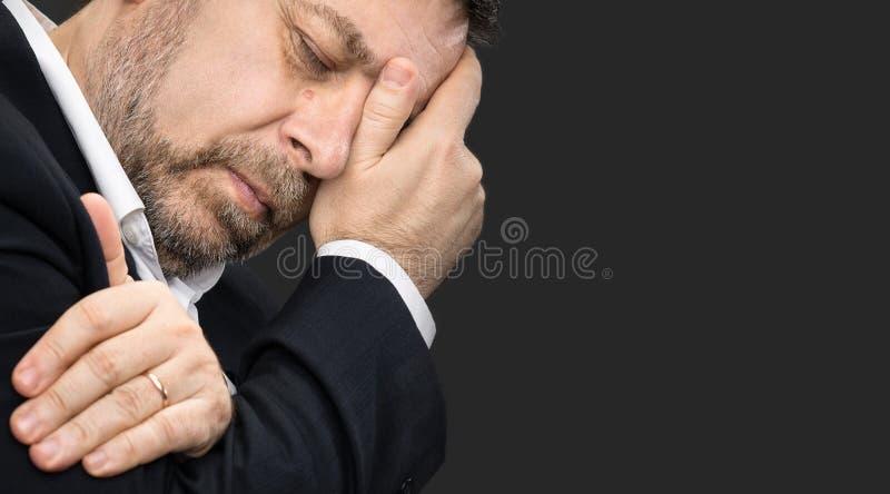 Huvudvärk Man med framsidan som stängs av handen royaltyfria foton