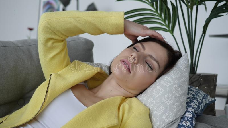 Huvudvärk spänd kvinna som hemma lägger på soffan royaltyfri bild