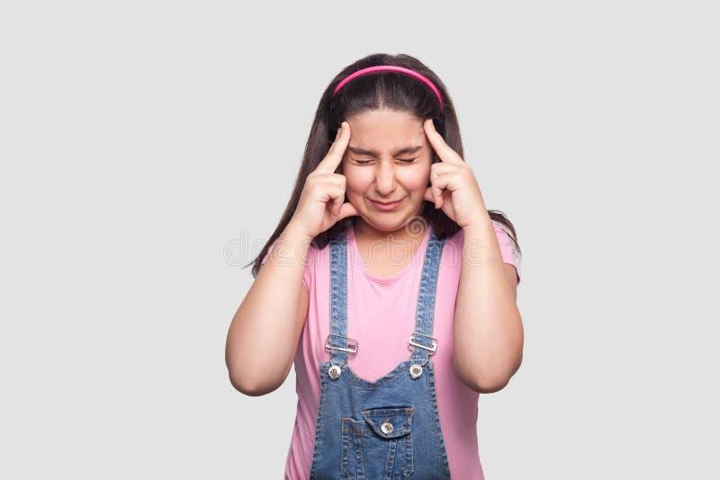 Huvudvärk, tänka eller förvirring Stående av bekymmerbrunettunga flickan i rosa t-skjorta och blåa overaller som står och rymmer  royaltyfria bilder