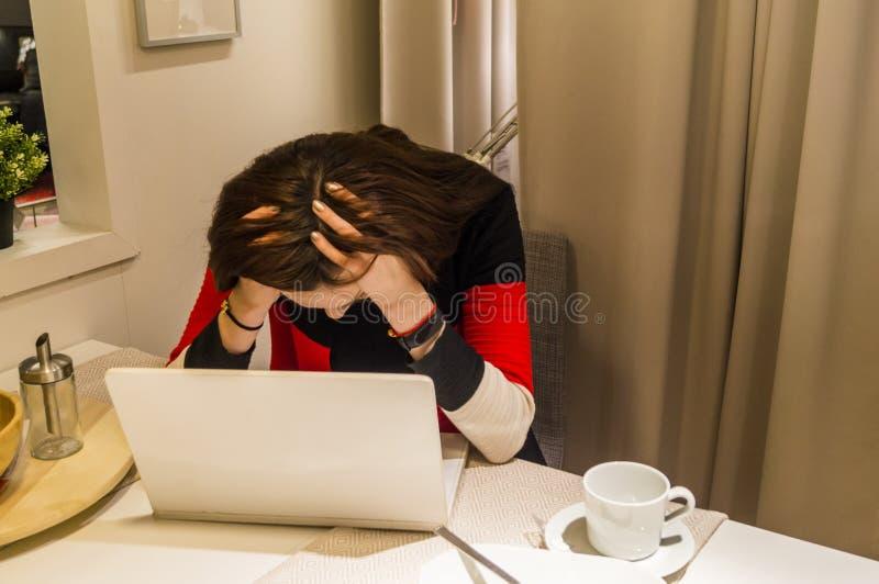 Huvudvärken från att arbeta på bärbara datorn anföll flickan royaltyfri foto