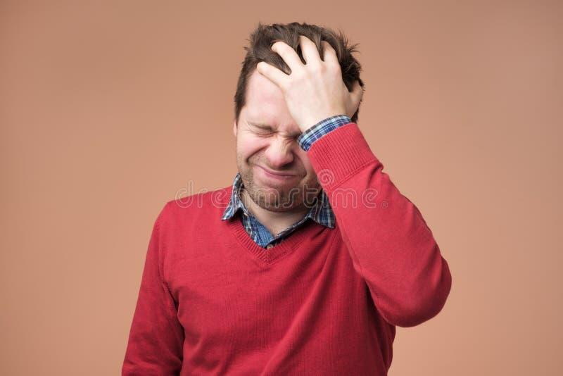 Huvudvärken och migrän, man med huvudet smärtar på brun bakgrund royaltyfria foton