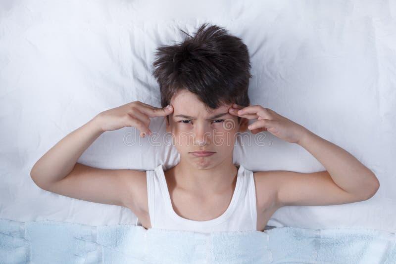 Huvudvärken pojken, i säng, på säng vilar, begreppet av sjukdomen arkivbilder