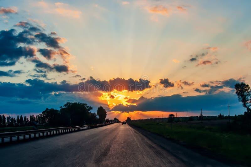 Huvudv?g med bilar som reser p? solnedg?ngen Horisontlinje med solen och stormmolnen resor royaltyfria foton