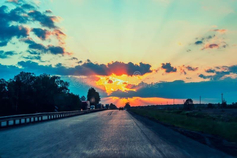 Huvudv?g med bilar som reser p? solnedg?ngen Horisontlinje med solen och stormmolnen resor Selektivt fokusera arkivfoton