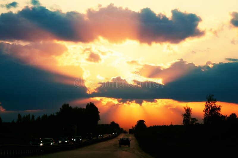 Huvudv?g med bilar som reser p? solnedg?ngen Horisontlinje med solen och stormmolnen resor Selektivt fokusera fotografering för bildbyråer