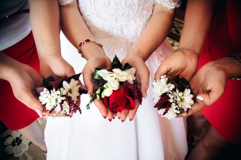 Huwelijk boutonies in de handen van de bruid en haar meisjes stock afbeeldingen