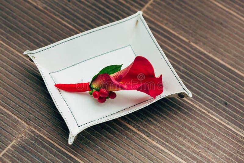 Huwelijk boutonniere van rode calla op het witte voetstuk Close-up kunstwerk stock foto's