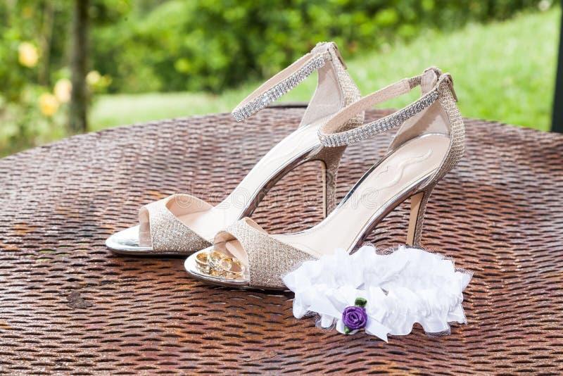 Huwelijk Bruidtoebehoren: liga, trouwringen dichtbij bruids schoenen op hoge hielen royalty-vrije stock foto's