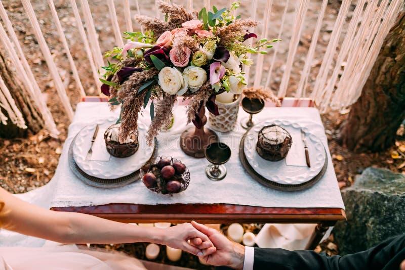 Huwelijk in de uitstekende stijl op openlucht Koppel holdingshanden De samenstelling van de bloem royalty-vrije stock foto