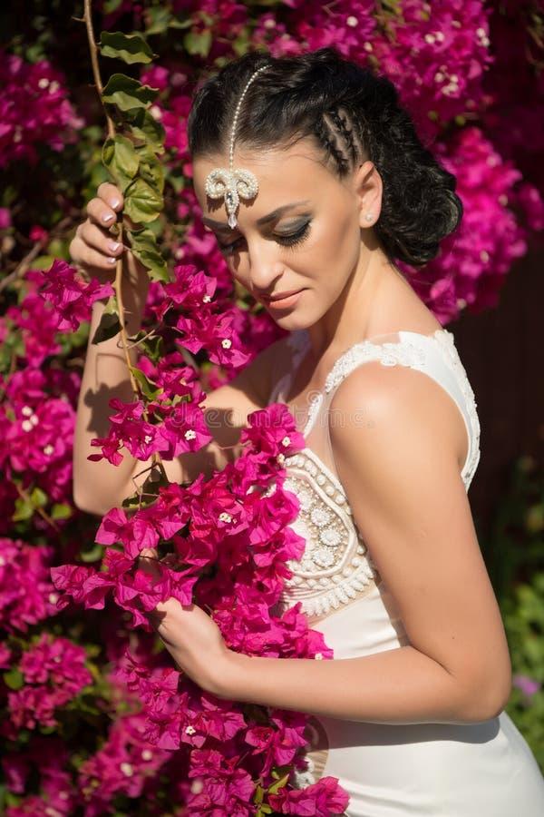 Huwelijk en de dagviering van vrouwen De vrouw stelt met tot bloei komende bloemen Mannequin met donkerbruin haar in tuin Wi van  royalty-vrije stock afbeelding
