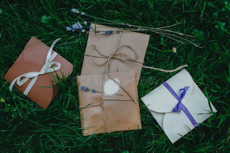 Huwelijk of partij liggen de decoratieve enveloppen op het groene gras Ivoor, bruine en violette kleuren Koorden en lavendel rust stock afbeeldingen