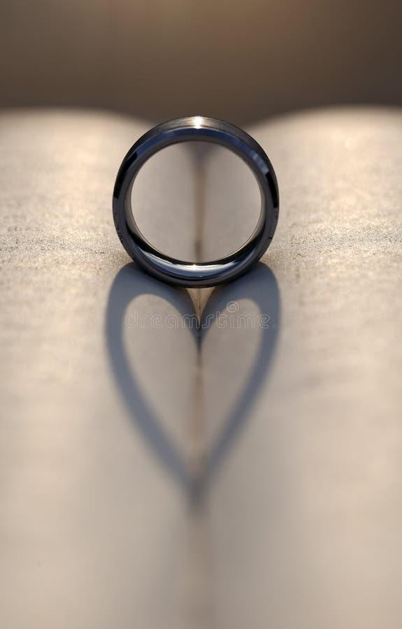 Huwelijk Ring Casting een Hartschaduw tussen Pagina's van een Boek royalty-vrije stock afbeelding