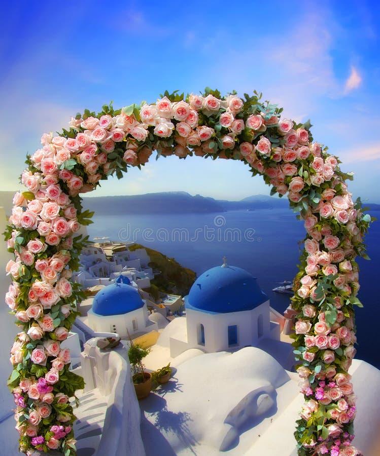 Huwelijk in Santorini Mooie die boog met bloemen van rozen met blauwe kerk van Oia, Santorini, Griekenland bij het meest romantis royalty-vrije stock afbeeldingen